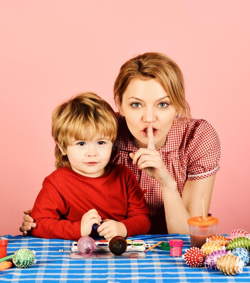 Μητέρα και γιος που κάνουν τις διακοσμήσεις Πάσχας Γυναίκα και παιδί με τα ευτυχή πρόσωπα στο ρόδινο υπόβαθρο Το Mom και το αγόρι στοκ φωτογραφία με δικαίωμα ελεύθερης χρήσης