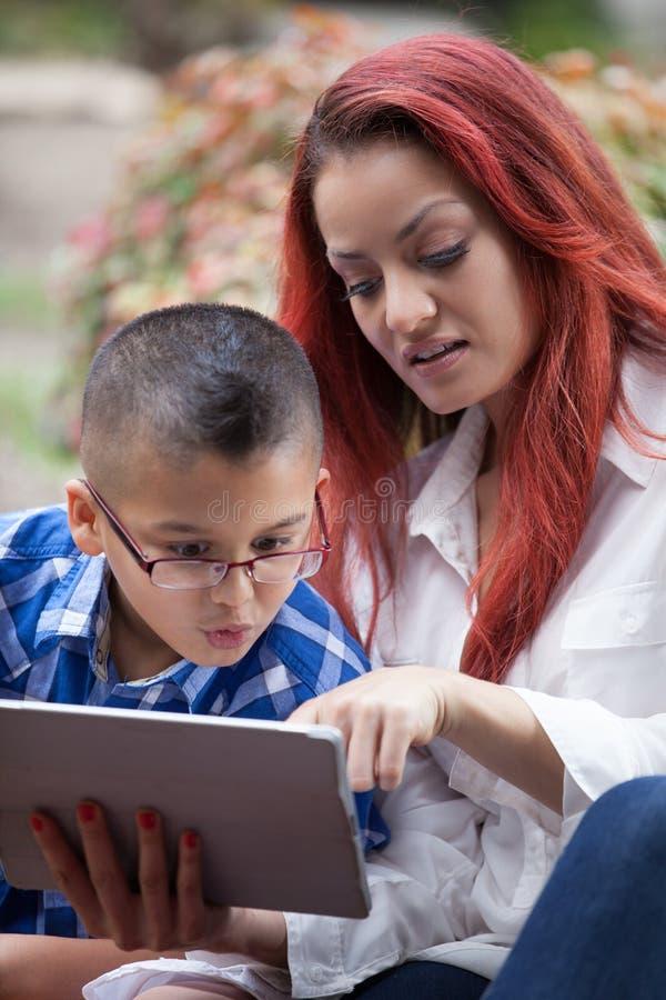 Μητέρα και γιος που μαθαίνουν από ένα μαξιλάρι αφής στοκ φωτογραφίες