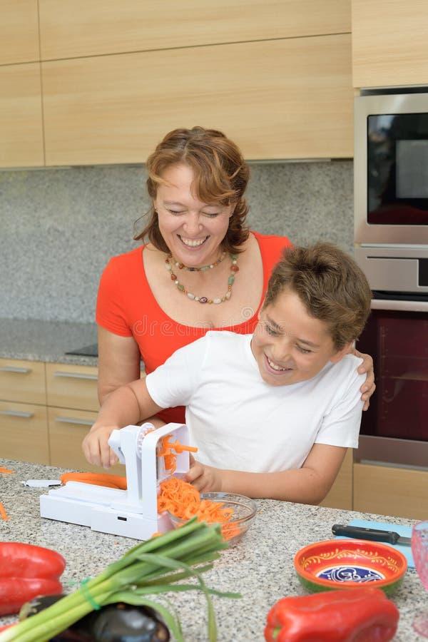Μητέρα και γιος που προετοιμάζουν το μεσημεριανό γεύμα και που γελούν με ένα κομμάτι του καρότου στοκ εικόνες με δικαίωμα ελεύθερης χρήσης
