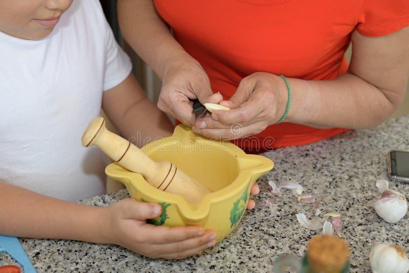 Μητέρα και γιος που προετοιμάζουν το μεσημεριανό γεύμα Τέμνον σκόρδο στοκ εικόνες με δικαίωμα ελεύθερης χρήσης