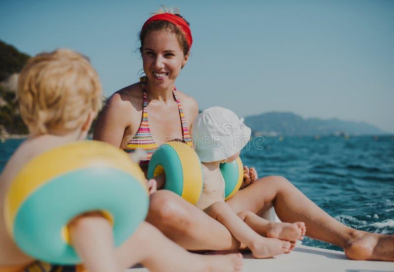 Μητέρα και δύο μικρά παιδιά μικρών παιδιών που κάθονται στην παραλία στις καλοκαιρινές διακοπές στοκ φωτογραφίες με δικαίωμα ελεύθερης χρήσης