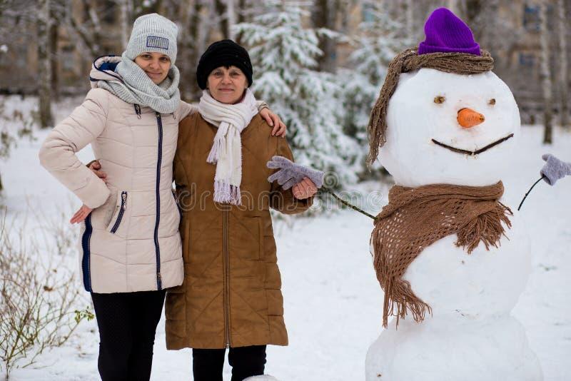Μητέρα και ενήλικη κόρη sculpt ένας μεγάλος πραγματικός χιονάνθρωπος στοκ φωτογραφία με δικαίωμα ελεύθερης χρήσης