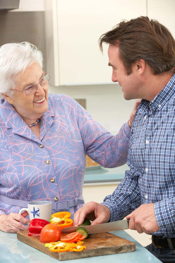 Μητέρα και ενήλικος γιος που προετοιμάζουν το γεύμα από κοινού στοκ εικόνες