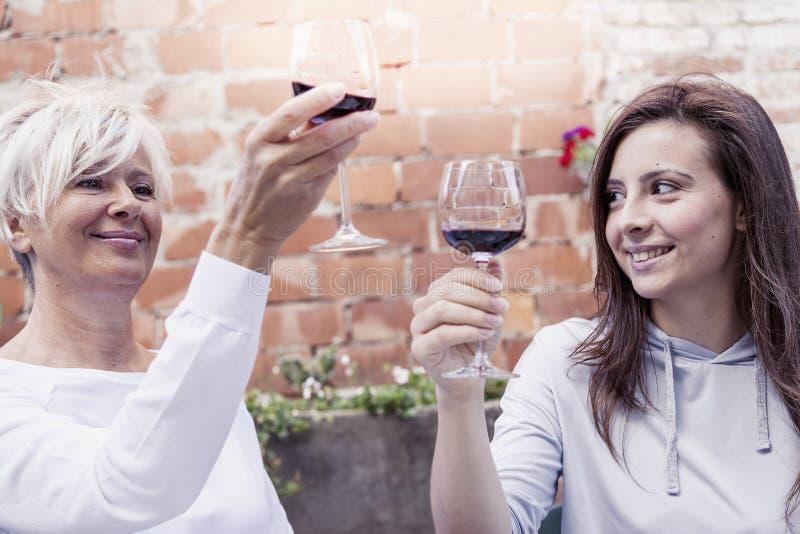 Μητέρα και ενήλικη συνεδρίαση κρασιού δοκιμής κορών υπαίθριες στοκ φωτογραφία με δικαίωμα ελεύθερης χρήσης