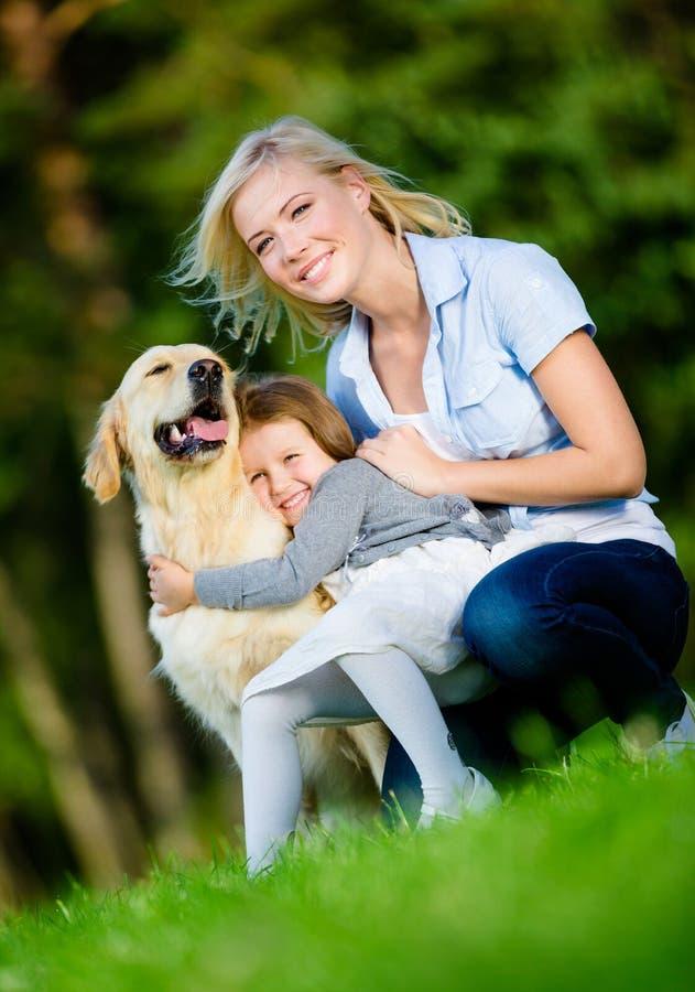 Μητέρα και κόρη με retriever στο πάρκο στοκ εικόνες
