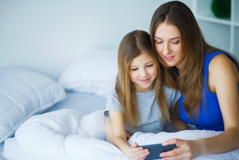 Μητέρα και κόρη που ακούνε τη μουσική στο κρεβάτι στοκ εικόνες