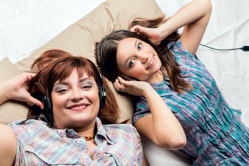 Μητέρα και κόρη που ακούνε τη μουσική στο κρεβάτι στοκ εικόνα με δικαίωμα ελεύθερης χρήσης
