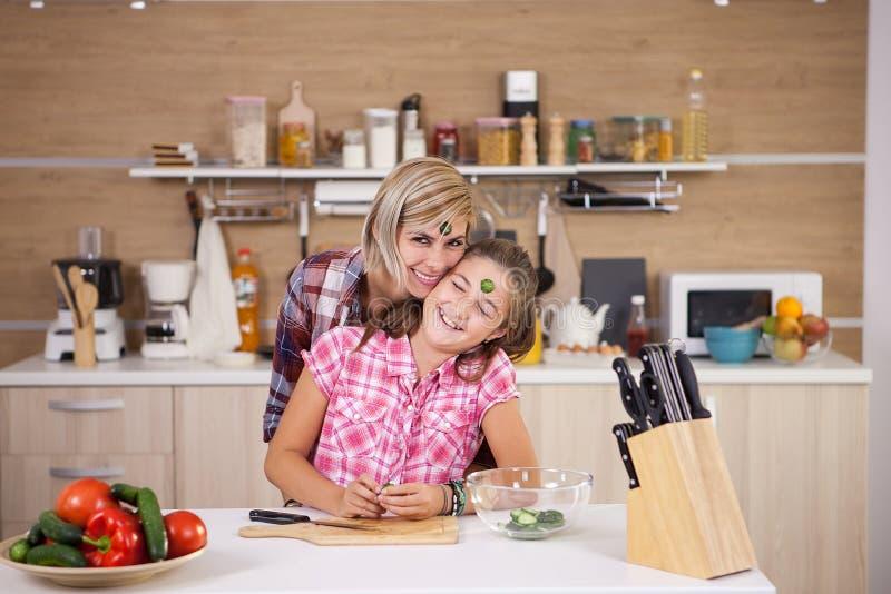 Μητέρα και κόρη που αστειεύονται γύρω ενώ μαγειρεύουν από κοινού στοκ φωτογραφίες