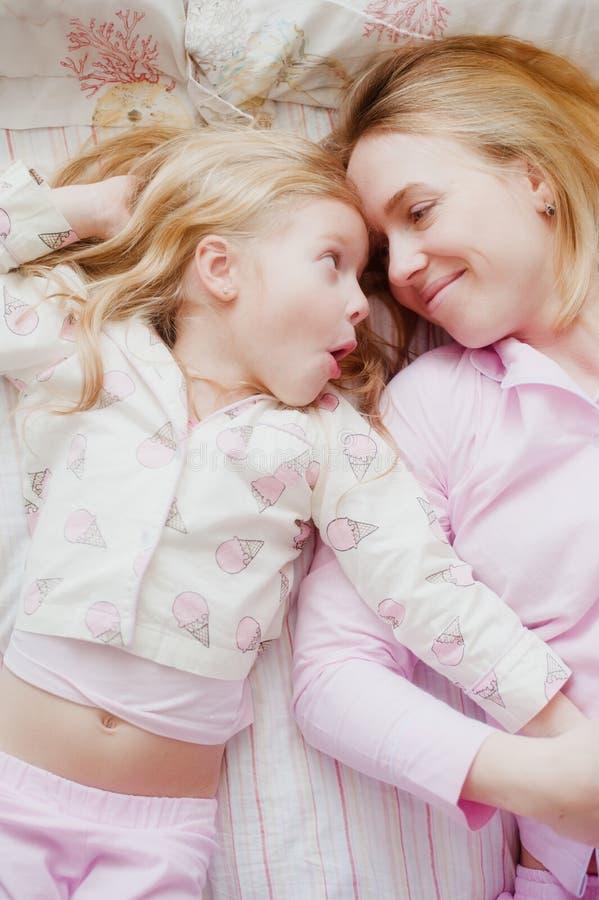Μητέρα και κόρη που βρίσκονται στο κρεβάτι στις ρόδινες πυτζάμες στοκ εικόνες