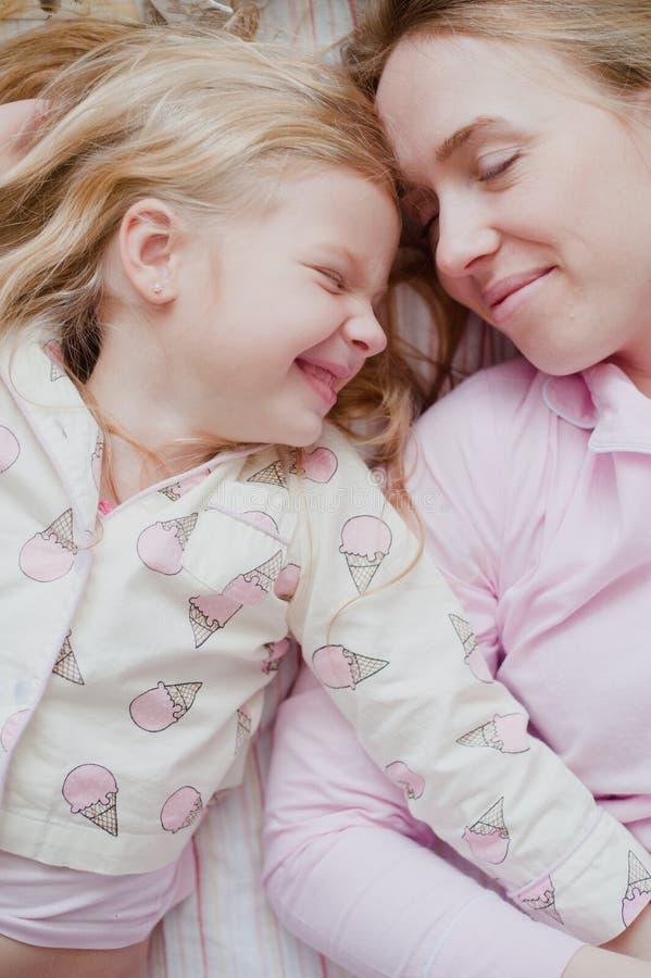 Μητέρα και κόρη που βρίσκονται στο κρεβάτι στις ρόδινες πυτζάμες στοκ φωτογραφία με δικαίωμα ελεύθερης χρήσης