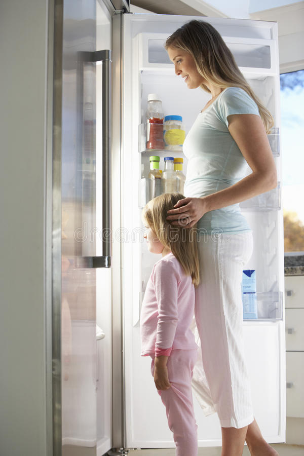 Μητέρα και κόρη που επιλέγουν το πρόχειρο φαγητό από το ψυγείο στοκ εικόνες