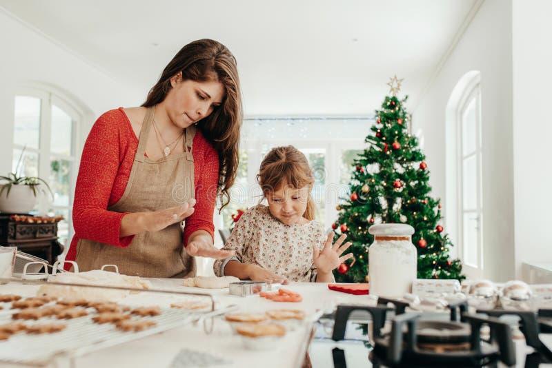 Μητέρα και κόρη που κατασκευάζουν τα μπισκότα Χριστουγέννων στοκ εικόνες με δικαίωμα ελεύθερης χρήσης
