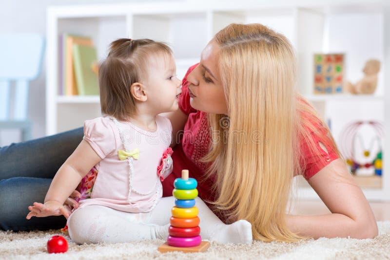 Μητέρα και κόρη που παίζουν και που χαμογελούν στο εσωτερικό στοκ εικόνες