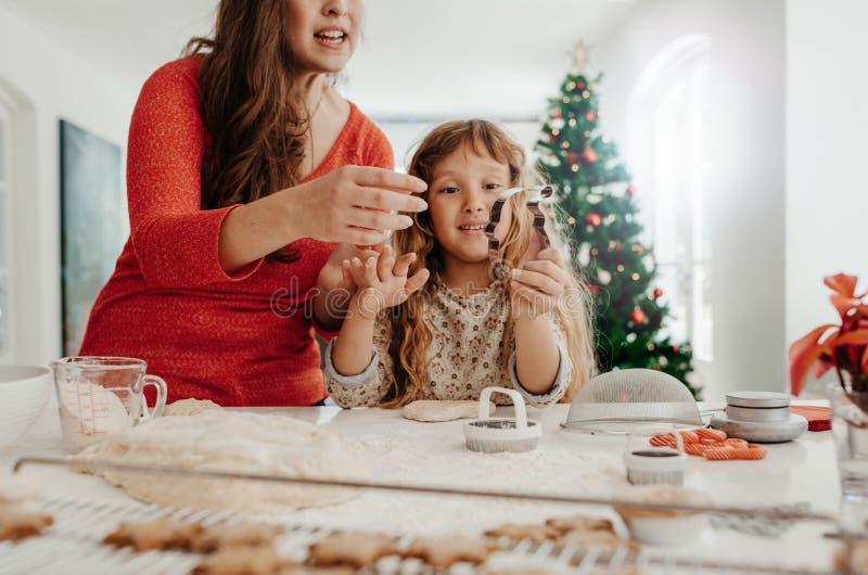 Μητέρα και κόρη που προετοιμάζουν τα μπισκότα Χριστουγέννων στοκ εικόνα