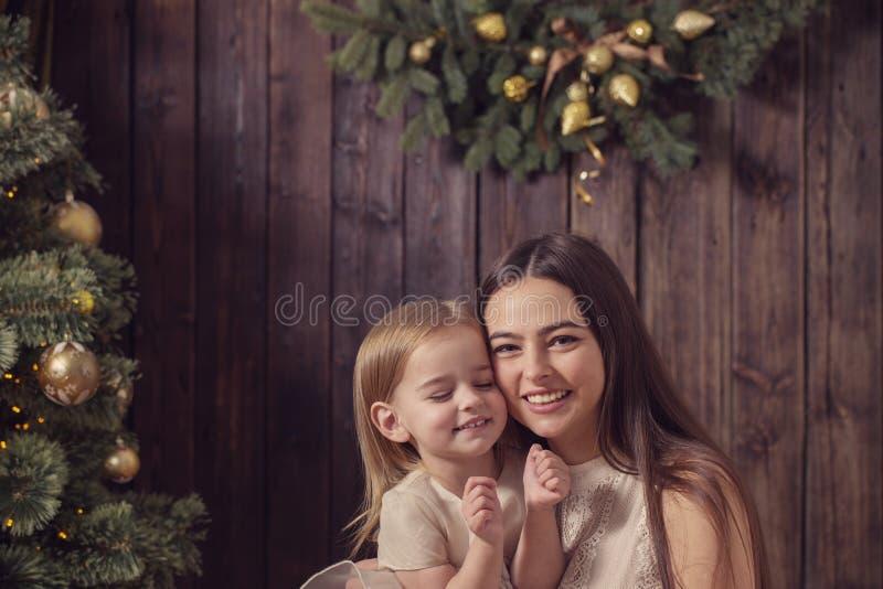 Μητέρα και κόρη στο χριστουγεννιάτικο δέντρο στο ξύλινο υπόβαθρο στοκ εικόνα