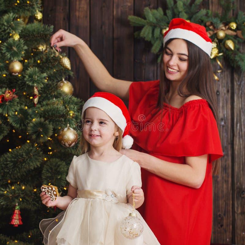 Μητέρα και κόρη στο χριστουγεννιάτικο δέντρο στο ξύλινο υπόβαθρο στοκ φωτογραφία με δικαίωμα ελεύθερης χρήσης
