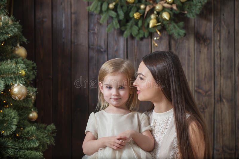 Μητέρα και κόρη στο χριστουγεννιάτικο δέντρο σε ένα ξύλινο υπόβαθρο στοκ φωτογραφίες με δικαίωμα ελεύθερης χρήσης