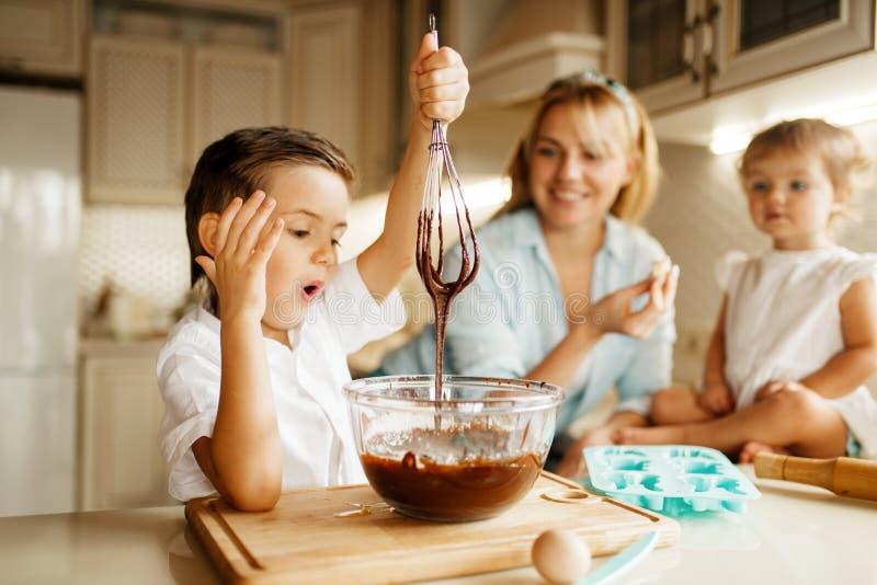 Μητέρα και λειωμένη η γούστα σοκολάτα παιδιών της στοκ εικόνα με δικαίωμα ελεύθερης χρήσης