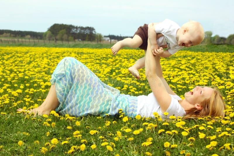 Μητέρα και μωρό που γελούν στις πικραλίδες στοκ φωτογραφίες με δικαίωμα ελεύθερης χρήσης