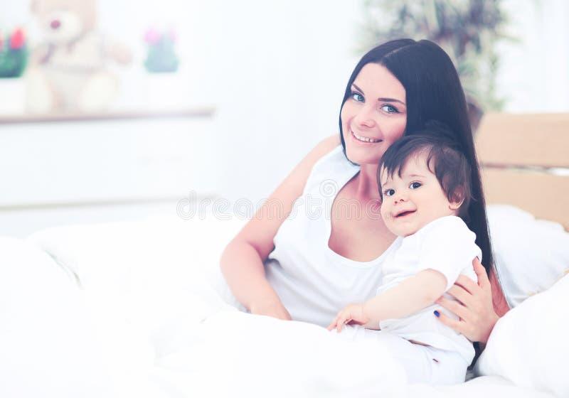 Μητέρα και μωρό στο παιχνίδι πανών στην ηλιόλουστη κρεβατοκάμαρα στοκ εικόνα