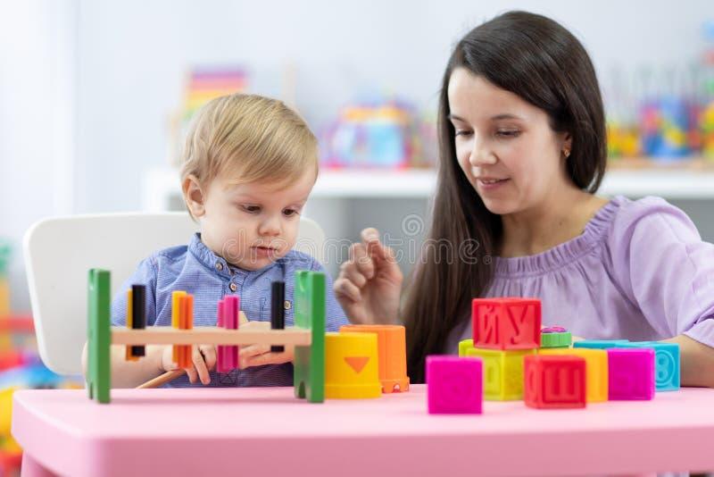 Μητέρα και παιδί γιος παίζουν μαζί με εκπαιδευτικά παιχνίδια στο σπίτι στοκ εικόνες