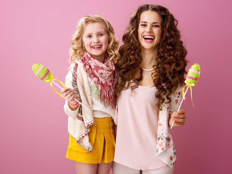 Μητέρα και παιδί που απομονώνονται στο ροζ με τα χειροποίητα αυγά Πάσχας στοκ φωτογραφίες