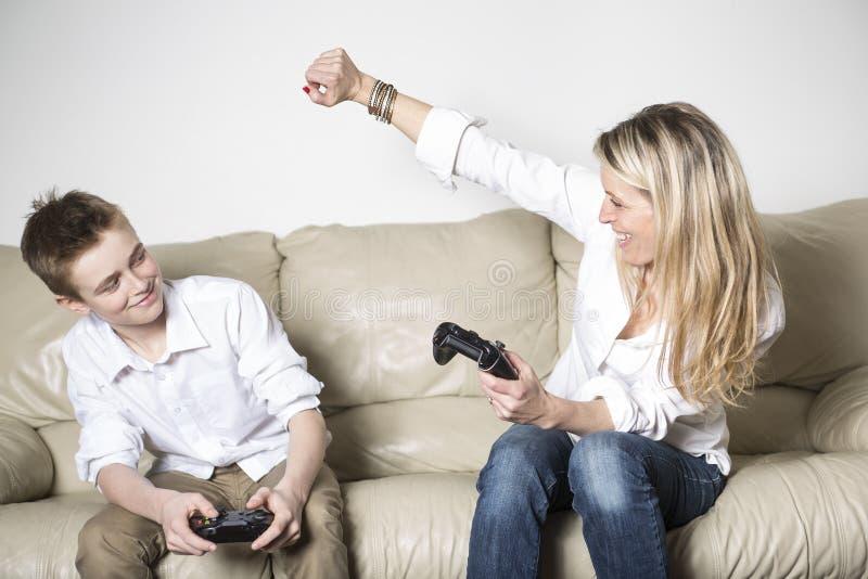 Μητέρα και παιδί που παίζουν ένα τηλεοπτικό παιχνίδι στοκ εικόνα