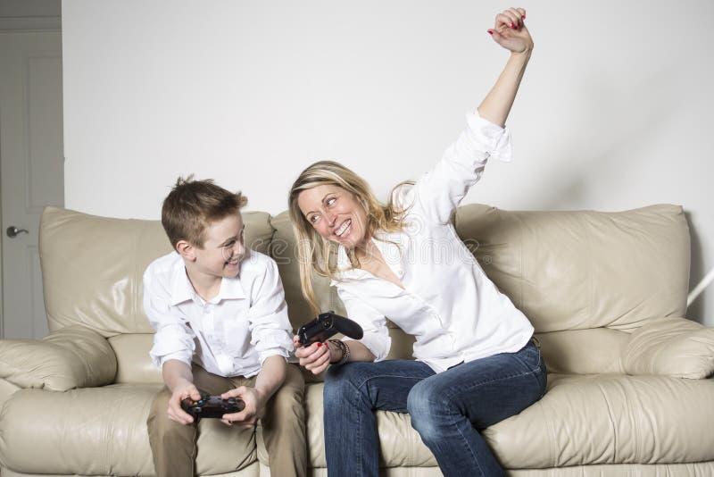 Μητέρα και παιδί που παίζουν ένα τηλεοπτικό παιχνίδι στοκ εικόνες