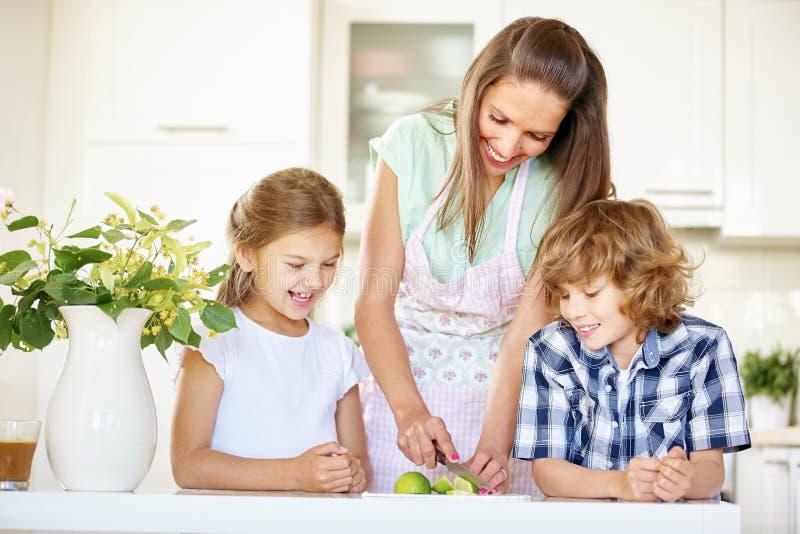 Μητέρα και παιδιά που κόβουν τα φρούτα ασβέστη στοκ εικόνες