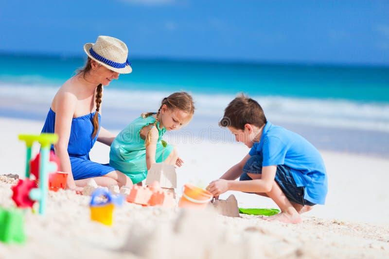 Μητέρα και παιδιά που παίζουν στην παραλία στοκ εικόνα με δικαίωμα ελεύθερης χρήσης