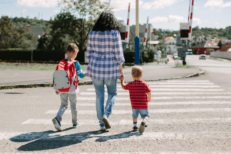 Μητέρα και τα παιδιά της που διασχίζουν το δρόμο στοκ φωτογραφία