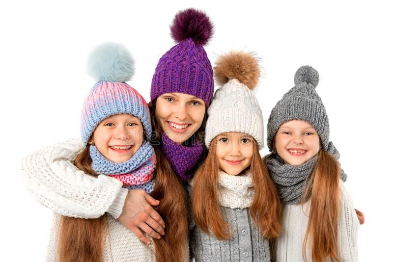 Μητέρα και χαριτωμένα παιδιά στα χειμερινά θερμά καπέλα και μαντίλι στο λευκό Χειμερινά ενδύματα παιδιών στοκ εικόνα με δικαίωμα ελεύθερης χρήσης