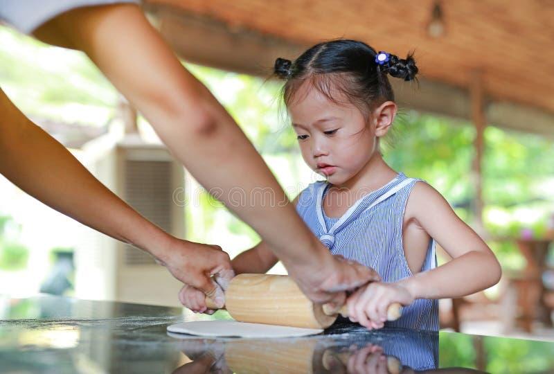 Μητέρα και χαριτωμένο μικρό κορίτσι που χρησιμοποιούν την ξύλινη κυλώντας καρφίτσα στη ζύμη για την πίτσα r στοκ εικόνες με δικαίωμα ελεύθερης χρήσης
