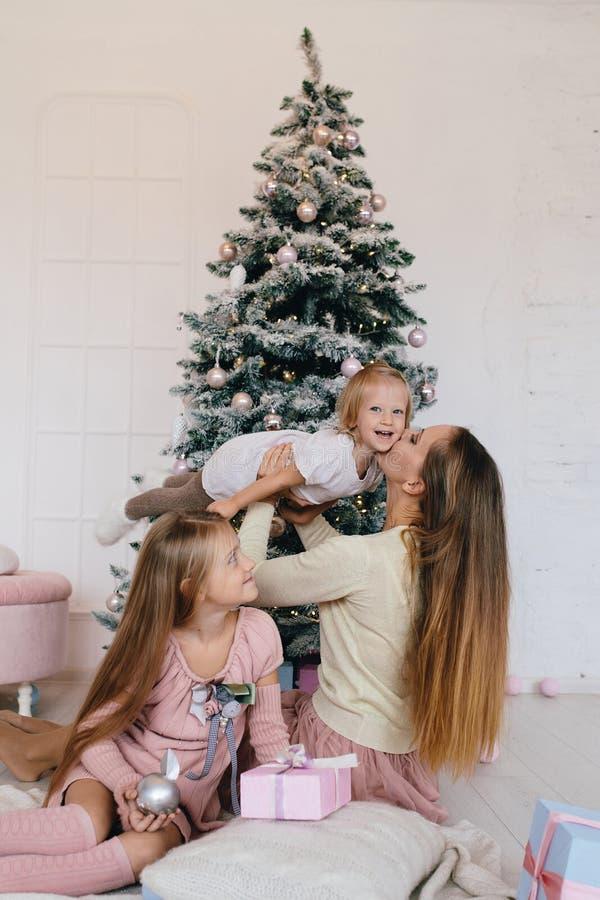 Μητέρα και δύο κόρες που παίζουν στο σπίτι κοντά στο χριστουγεννιάτικο δέντρο η ευτυχής οικογένεια έχει τη διασκέδαση για τις δια στοκ φωτογραφίες με δικαίωμα ελεύθερης χρήσης