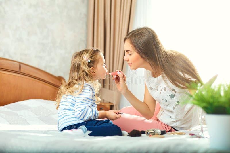 Μητέρα και daughter do make-up, παιχνίδι στο κρεβάτι από το παράθυρο στοκ φωτογραφία με δικαίωμα ελεύθερης χρήσης