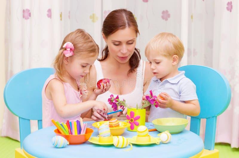 Μητέρα με τα αυγά Πάσχας χρωμάτων παιδιών στοκ φωτογραφίες με δικαίωμα ελεύθερης χρήσης
