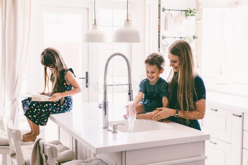 Μητέρα με τα παιδιά της που παίζουν στο νεροχύτη κουζινών στοκ φωτογραφίες με δικαίωμα ελεύθερης χρήσης