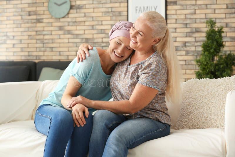 Μητέρα με την κόρη της μετά από τη χημειοθεραπεία στο σπίτι στοκ εικόνα