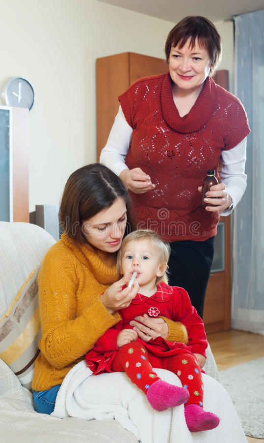 Μητέρα με την ώριμη γιαγιά που δίνει το φάρμακο στο αδιάθετο bab στοκ εικόνα με δικαίωμα ελεύθερης χρήσης