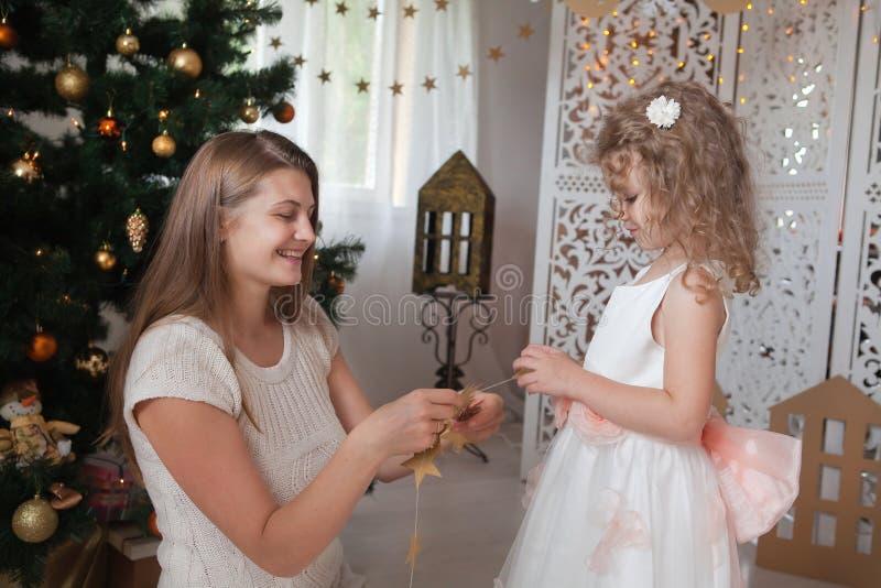 μητέρα με τη γιρλάντα Χριστουγέννων λαβής κορών αστεριών της στα χέρια τους στοκ φωτογραφία με δικαίωμα ελεύθερης χρήσης