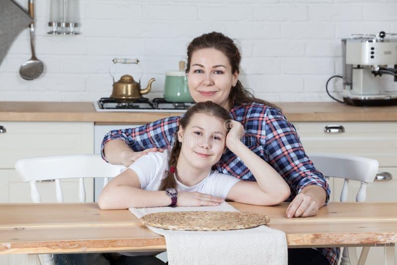 Μητέρα με τη συνεδρίαση έφηβη κόρη της στον πίνακα στην κουζίνα μαζί, που εξετάζει τη κάμερα στοκ φωτογραφίες με δικαίωμα ελεύθερης χρήσης