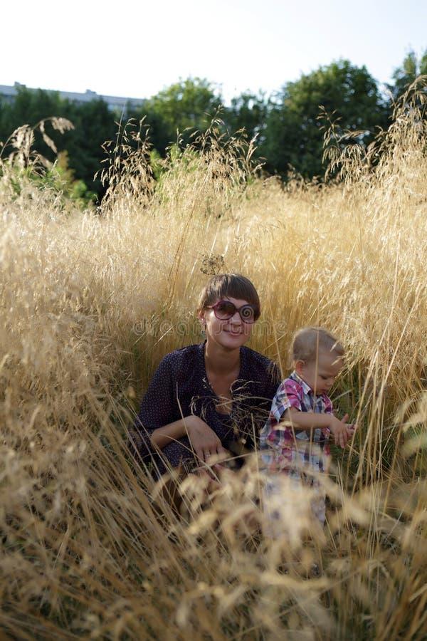 Μητέρα με τη συνεδρίαση γιων στον τομέα της χλόης στοκ φωτογραφίες