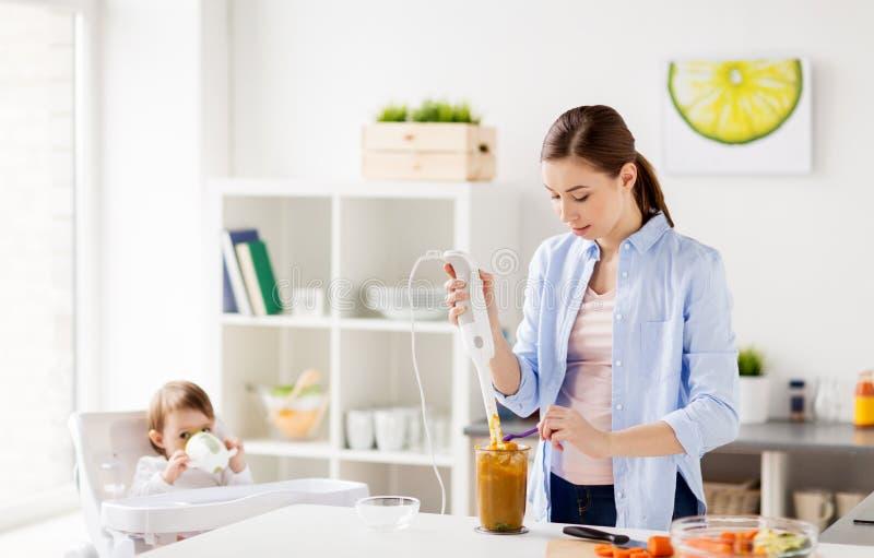 Μητέρα με τις μαγειρεύοντας παιδικές τροφές μπλέντερ στο σπίτι στοκ φωτογραφία με δικαίωμα ελεύθερης χρήσης