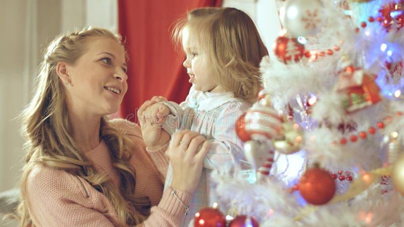 Μητέρα με το λατρευτό μωρό που έχει τη διασκέδαση και το φιλί μεταξύ τους στο χριστουγεννιάτικο δέντρο στο σπίτι στοκ φωτογραφίες