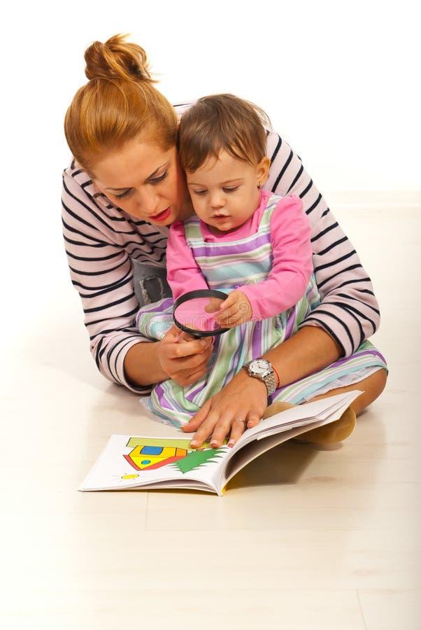 Μητέρα με το βιβλίο ανάγνωσης κοριτσιών στοκ φωτογραφία με δικαίωμα ελεύθερης χρήσης
