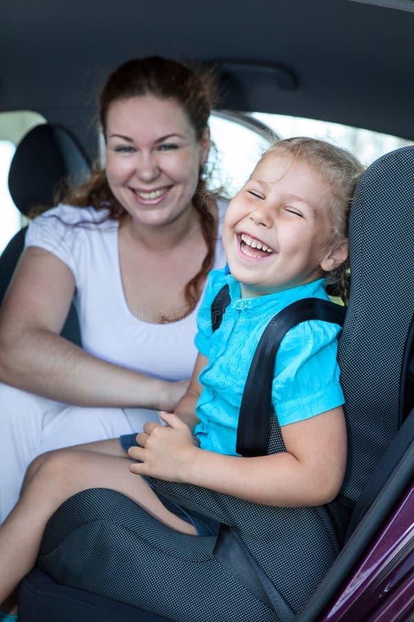 Μητέρα με το μικρό γέλιο κορών στη πίσω θέση του αυτοκινήτου στοκ φωτογραφία