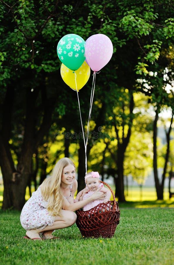 Μητέρα με το μικρό κορίτσι στο υπόβαθρο των πράσινων δέντρων κορίτσι μπουκαλιών μωρών στοκ φωτογραφία με δικαίωμα ελεύθερης χρήσης
