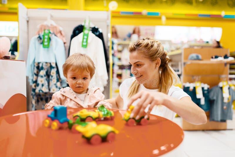 Μητέρα με το μικρό κορίτσι της που παίζει στο κατάστημα παιδιών στοκ εικόνα με δικαίωμα ελεύθερης χρήσης