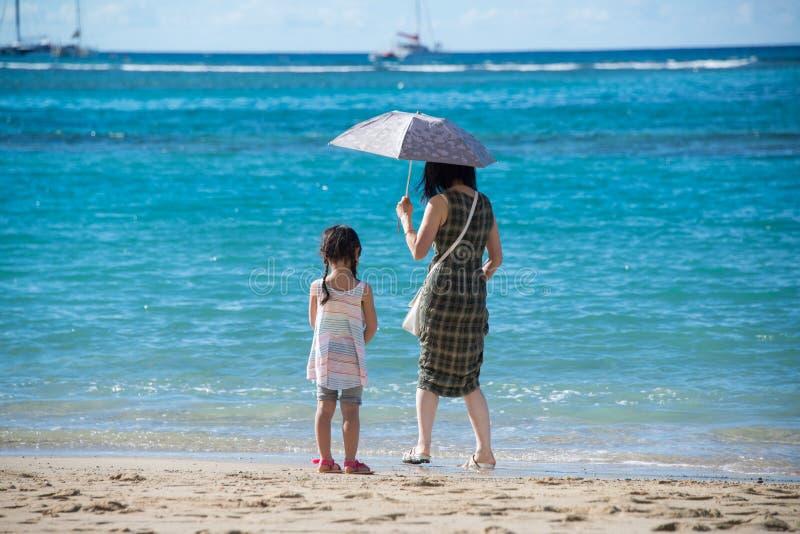Μητέρα με το περπάτημα παιδιών ομπρελών και μικρών κοριτσιών στην αμμώδη παραλία στον ωκεανό στοκ φωτογραφία με δικαίωμα ελεύθερης χρήσης