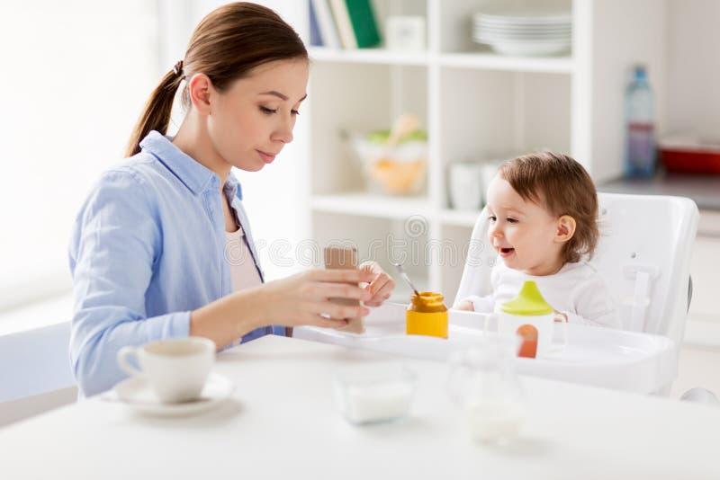 Μητέρα με το smartphone και μωρό που τρώει στο σπίτι στοκ εικόνες με δικαίωμα ελεύθερης χρήσης
